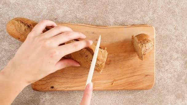 Ženské ruce jsou řezání čerstvý žitný bagetu na dřevěném prkénku. Šedé béžové pozadí. Pohled shora