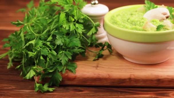 Čerstvé, chutné pyré brokolicová polévka v hliněné misky s ingrediencemi na prkénku. Pojem zdravé potraviny. Rustikální dřevěné pozadí. Horizontální zobrazení