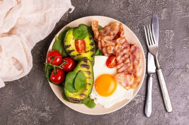 Grilled bacon and avocado, fried eggs with spinach and cherry tomatoes on gray concrete background. Ketogenic diet. Low carb high fat breakfast. Healthy food concept