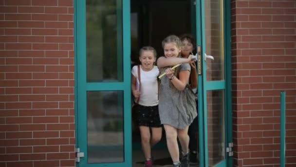 Čtyři žáci se baví po vyučování. Nosí školní uniformu. Budova školy je na pozadí