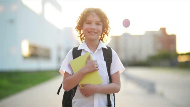 Šťastný roztomilý chytrý chlapec s školní tašku a knihou v ruce. Moderní batoh. Dítě je připraveno na odpověď. Poprvé do školy. Zpátky do školy.