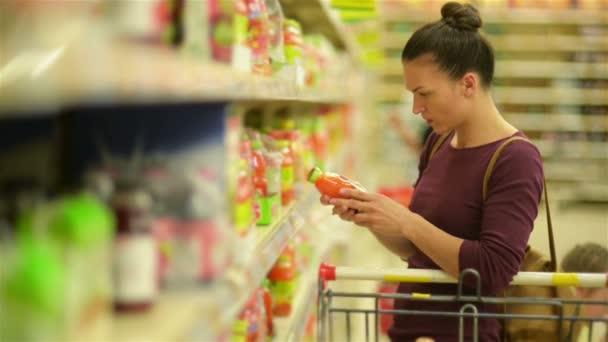 Young Woman Chooses Juice From the Supermarket Shelf. She Has A Lot of Items in Her Supermarket Cart.