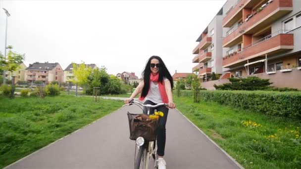 Portrait of Happy Young Woman on Bicycle. In Her Bicycle Basket Are Flowers And A Bag. She Enjoys The Trip.