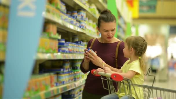 Cutie Girl with Caucasian Appearance is Eating Lollipop and Sitting in Supermarket Trolley. Mother On Background Chooses Baby Food For Her Daughter.