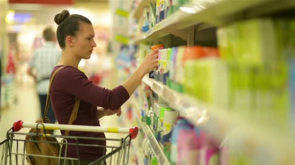 Beautiful Women Chooses Spray. A Supermarket Cart with Products Near Her.