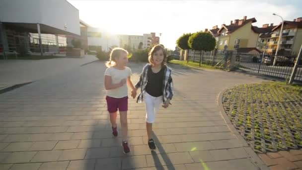 Boy And Girl Run Together Holding Hands On Asphalt. They Have A Lot of Fun.