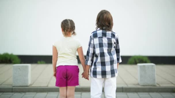 A Couple of Children Stand Back and Hold on to Their Hands. The Wind Waves Their Blond Hair.