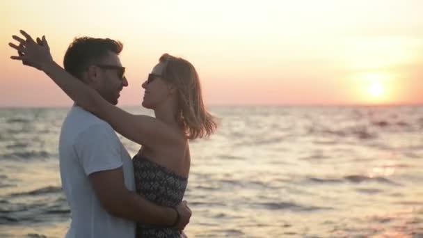 Pár objímání a líbání na pláž pohledu ven na moře při západu slunce