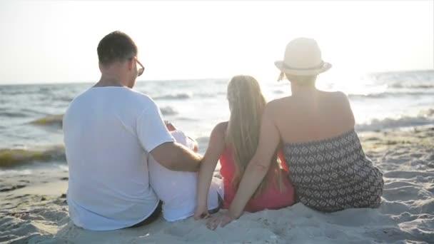 Venku portrét matka, otec, Dcera a syn sedí na pláži poblíž moře a objímání při pohledu na slunce a vlny.