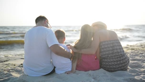 Rückansicht von Mutter, Vater, Tochter und Sohn, die am Strand am Meer sitzen und sich umarmen und Sonne und Wellen betrachten.