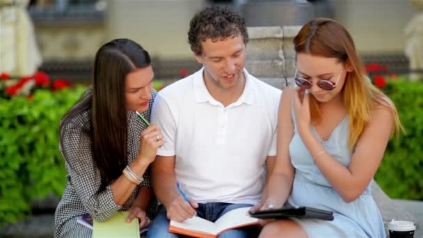 One Handsome Boy in White Shirt and Jeans Sitting near Two Beautiful Girls in Summer Dresses Studing Together Outdoors During Warm Sunny Day.