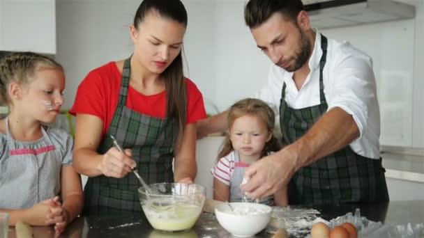 Famiglia felice che cucina insieme. Giovani figlie stanno aiutando ai loro genitori. Hanno un sacco di divertimento.