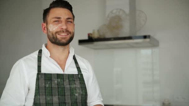 glücklicher Koch in Schürze posiert und lächelt. Er hat viel Freude am Kochen.