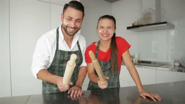 Paar, das zusammen ein lustiges Gesicht macht. bärtige Männer und Mädchen mit kaukasischem Aussehen in Schürzen in der modernen Küche.