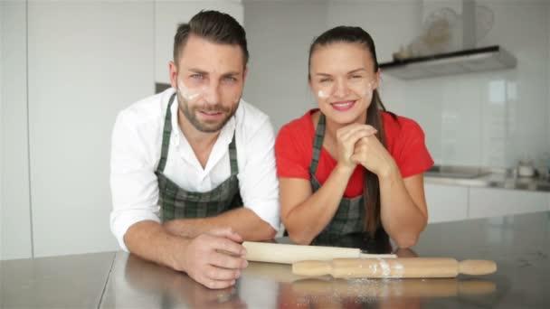Egy pár jelentő és néz a kamerába. Nekik van egy csomó szórakoztató együtt Staiyng, Modern konyha.