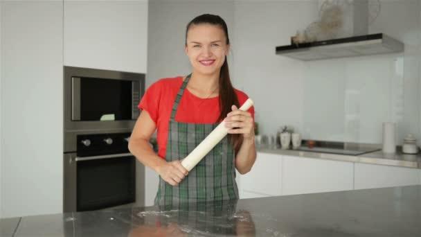 junge lächelnde kaukasische Hausfrau in gestreifter Schürze. rotes T-Shirt isoliert auf Küchenhintergrund. schönes Porträt der Haushälterin.