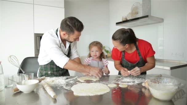 Roztomilá holčička a její krásné rodiče jsou vaření. Mají spoustu zábavy dohromady a usmívající se v kuchyni doma. HD, tři, šťastná rodina.