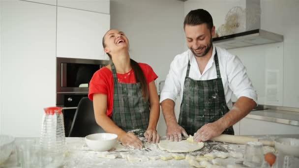 glückliches Paar beim gemeinsamen Kochen in der Küche. Sie haben jede Menge Spaß dabei, Teig zu kneten und miteinander zu lachen.