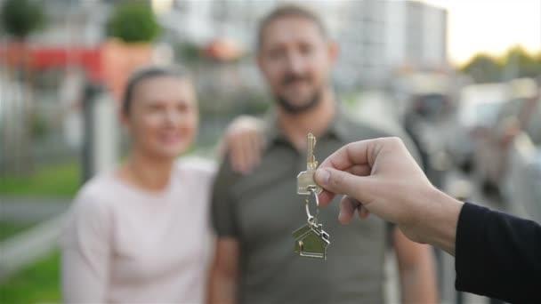 Ruka muže realitní Agent dává klíče k majitelům nového domu. Šťastný pár