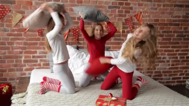 Trojčata sestry oblečený v vánočními pyžama mají polštář bojovat na posteli, který je zařízen na Vánoce, Veselé Vánoce a šťastný nový rok