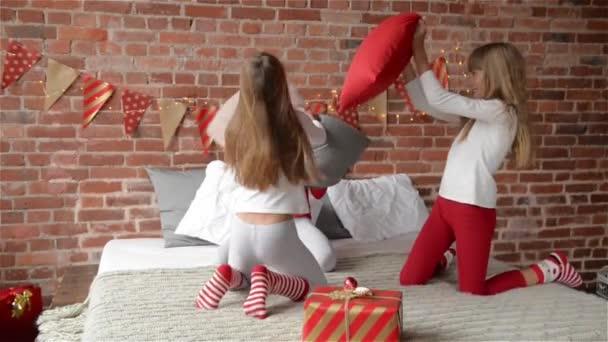 Boldog nevető hármas nővérek pizsamában, miután egy párnát harcot az ágyban otthon. A hálószobában van díszítve a karácsonyfa számára füzérek és karácsonyi ajándékok, karácsonyi ünnepeket