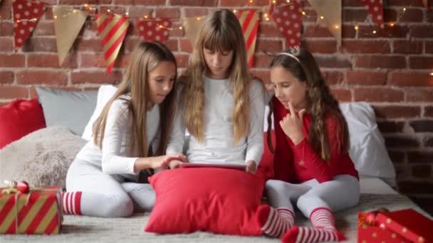 Trojčata sestry oblečený v pyžamu vánoční posezení v ložnici se baví s digitální tablet, který přinesl ji domů zdobené pro vánoční Santa Claus.