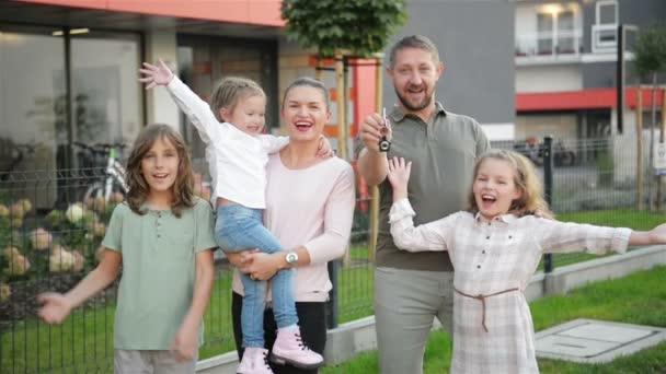 Familie mit Kindern schaut in die Kamera, die draußen auf der Straße steht. Paar und Kinder kaufen ein neues Zuhause. Immobilienbesitzer mit Schlüsseln umarmen sich und posieren mit Sohn und Tochter. Hypothekendarlehen. hd, zusammen