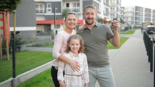 Happy Family With Kids Standing Outdoor Holding Keys Of Big Country House. Smiling Luxury Real Estate Owners Couple And Children Embracing On Street After Buying New Home. Mortgage Loan Concept.