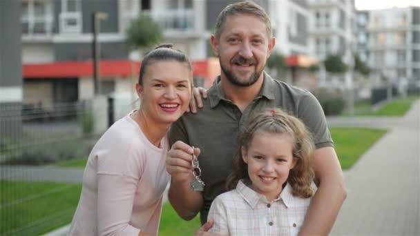 Šťastná rodina s dětmi stojící venkovní držení klíče velký venkovský dům. Usmívající se pár luxusních vlastníci nemovitostí a děti objímat na ulici po koupi nového domova. Hypoteční úvěr koncept.