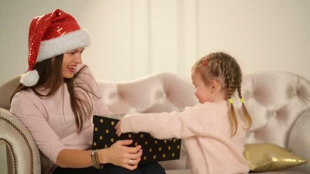 Die fröhliche Mutter und ihr süßes Töchterbaby öffnen ein Geschenk. Eltern und kleine Kinder vergnügen sich in der Nähe des Weihnachtsbaums im Haus. liebe Familie frohe Weihnachten und ein glückliches neues Jahr.