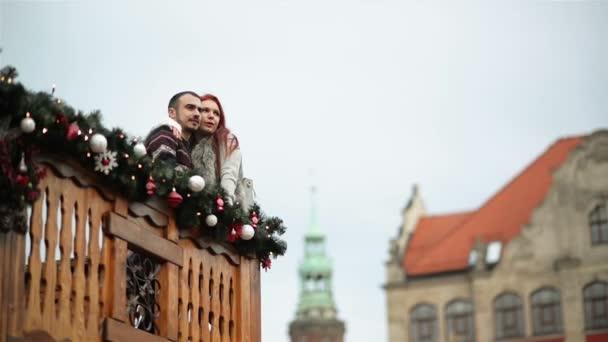 Pár milenců se mazlení se sebou. Stojí na dřevěném balkoně během vánočního času. Šťastný nový rok koncepce.