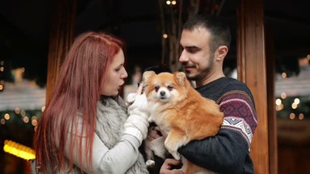 Mladý pár bavit venku v době Vánoc. Oni se drží Cutie psy. Šťastný nový rok koncept. HD, společně, domácí zvířata, světla