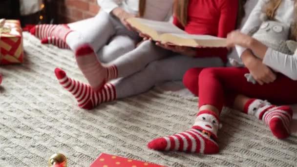 Tři sestry, sedí na posteli v měkké pyžamo, trojčata dívky číst knihu vánoční příběhy, ložnici zdobí vánoční osvětlení a dary