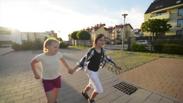 Mutlu çocuklar birlikte çalışan tutuşup yolda. Güneş ışınlarının yüzlerine parlaklık.