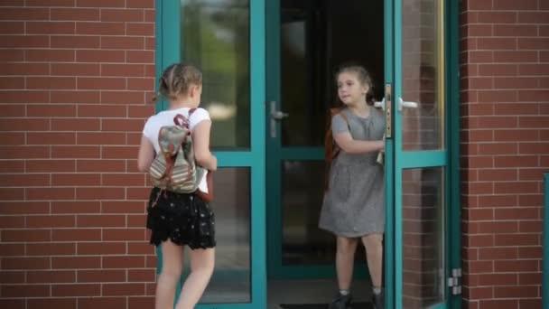 Gruppe von Grundschülern, die in der Schule laufen. Sie haben eine Menge Spaß. sie reden miteinander.
