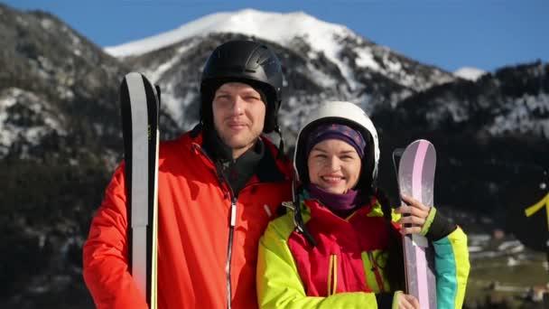 Portrét mladého usmívající se pár v hoře. Mají dobrou náladu trávit zimní dovolenou společně.