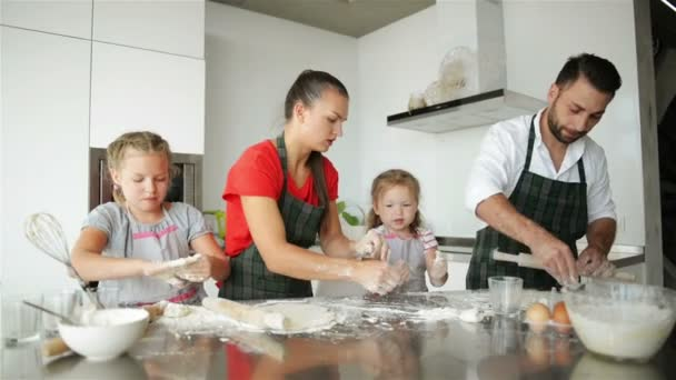 Family Cooking Together. They Have a Lot of Fun Playing On Kitchen. Cute Daughters With Their Handsome Parents Playing with Flour. They Are Smiling While Cooking.