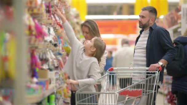 Belle coppie e la loro figlia si divertono mentre si fa Shopping nel supermercato.