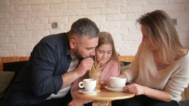 Rodina v Cafe. Rodina je matka, otec a dcera. Lidé sedí u stolu. Jsou spokojení a s úsměvem. Rodinný portrét. Slunečného dne.