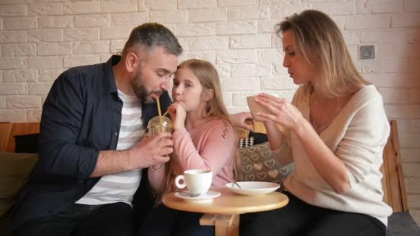 Portrét šťastné rodiny trávit čas spolu v Cafe. Mají spoustu legrace mluvit k sobě navzájem.