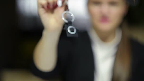 Selektivní zaměření obchodní dámy držení nového klíče domu a usmívající se. Zavřít portrét agenta realitní kanceláře.