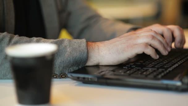 Közelről megtekintése szabadúszó dolgozó laptop Siting az Internet Cafe beltéri. Fiatal szakállas ember írása szöveg megnyomásával gombok laptop. Online munka, szabadúszó, Office.