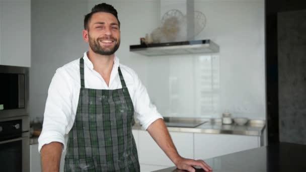 schöner bärtiger Mann in Schürze, der in der Küche posiert. er sieht so glücklich aus.