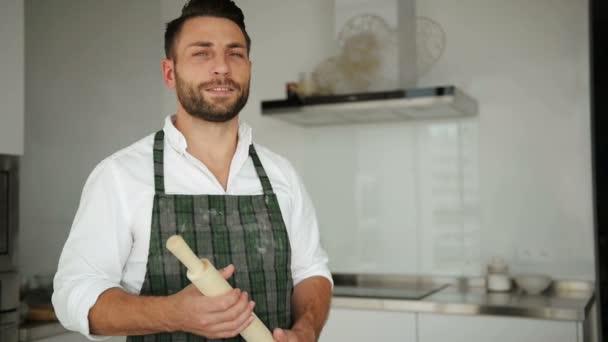 Porträt eines jungen gutaussehenden kaukasischen Chefkochs in Schürze. er übernachtet in einer modernen, hellen, geräumigen Küche.