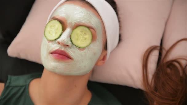 Heimbad. drei Frauen mit Gurkenstücken im Gesicht, die auf dem Bett liegen. Schönheitssalon Konzept, Gesundheit.