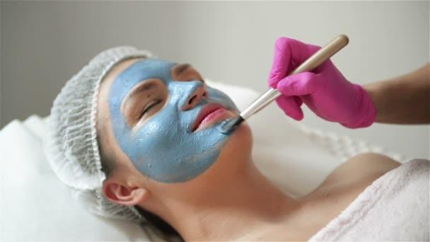 Kosmetologe macht Verfahren zur Reinigung und Feuchtigkeitsversorgung der Haut. Maske mit speziellem Pinsel auf Gesicht der Frau auftragen. junges Mädchen pflegt ihre Haut. besucht kosmetologische Klinik. Ästhetische Medizin.