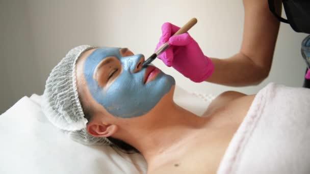 Arc peeling maszk, Spa Beauty kezelés, Skincare. Nő Getting Arcápolás a kozmetikus a Spa Salon. Nő tesz Alginate maszk. Lány a maszk a bézs Clay.