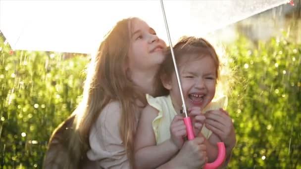 Kinder mit bunten Regenschirm spielen im Herbst Brauseregen. Kleine Mädchen spielen im Park, bei Regenwetter. Herbst-outdoor-Spaß für Kinder.