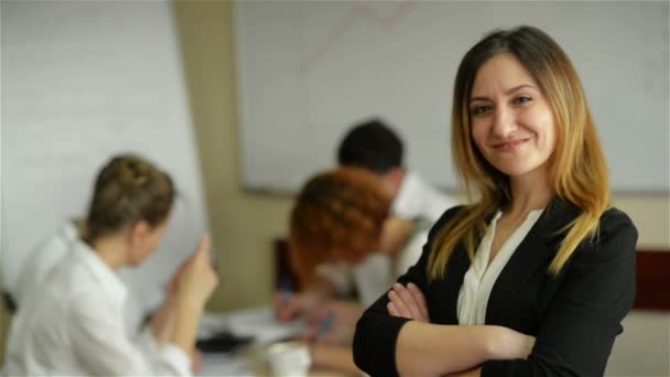 Beautiful young grinning professional woman in office, folded arms and confident expression as other workers hold a meeting in background