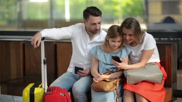 Rodina čekající na váš let nebo vlak a používání telefonů při sezení v čekárně na letišti nebo na nádraží.
